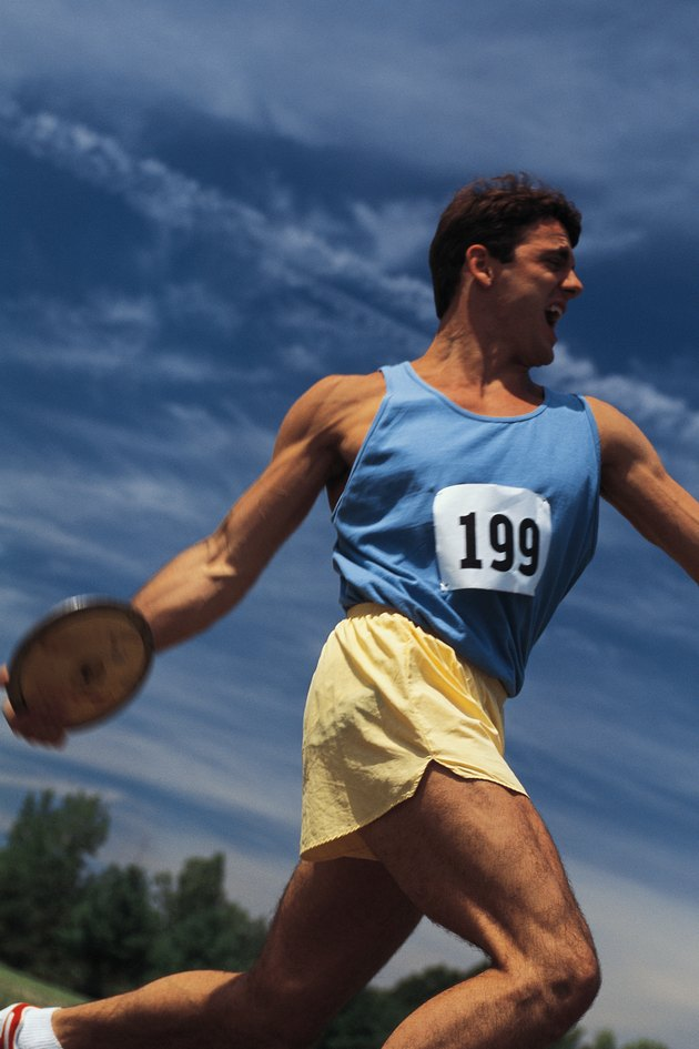 Young man throwing discus