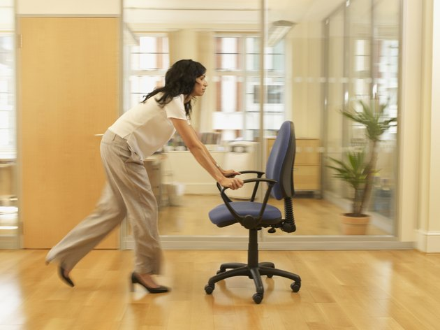 Hispanic businesswoman pushing office chair