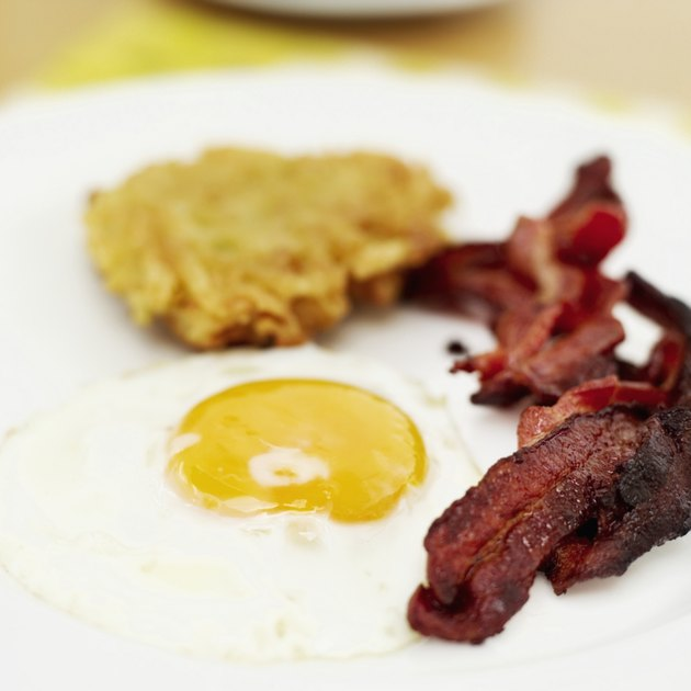 Close-up of a fried egg with bacon and hash browns on a plate