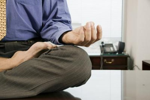 Businessman meditating barefoot on desk