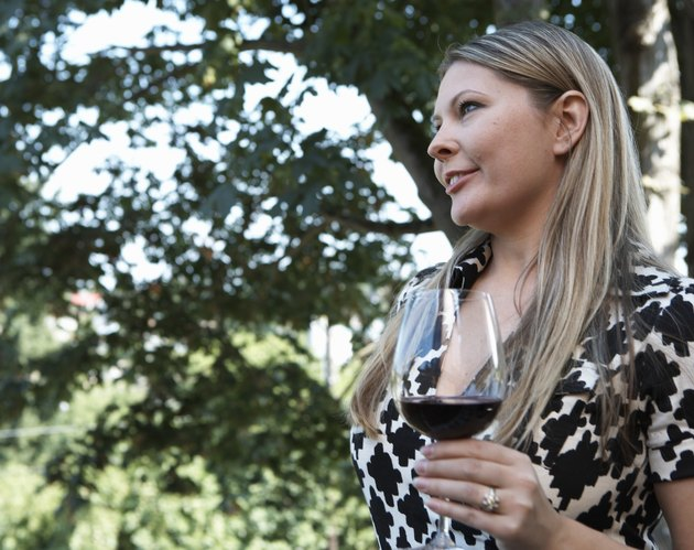 Woman with glass of red wine outdoors, side view