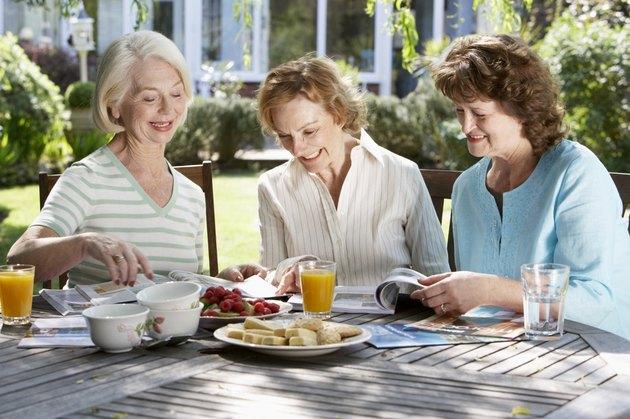 Three senior women in garden looking at holiday brochures, smiling