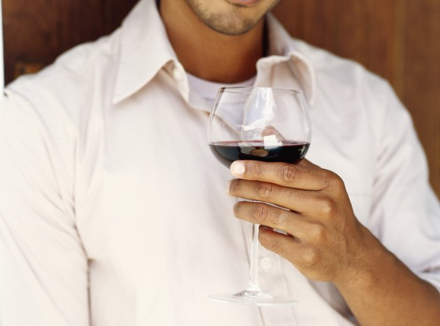 Young man drinking glass of red wine, close-up