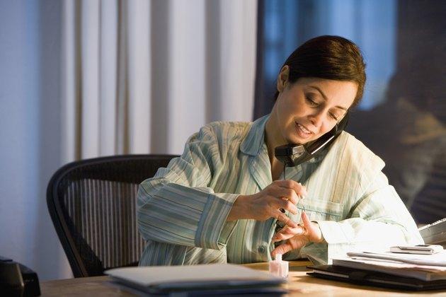 Hispanic businesswoman painting fingernails at desk