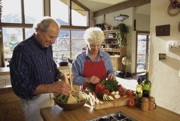Elderly couple making a salad together