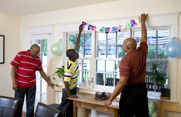 Men and boy hanging birthday decorations