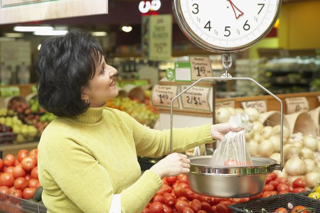 Mid adult woman weighing vegetables in a supermarket