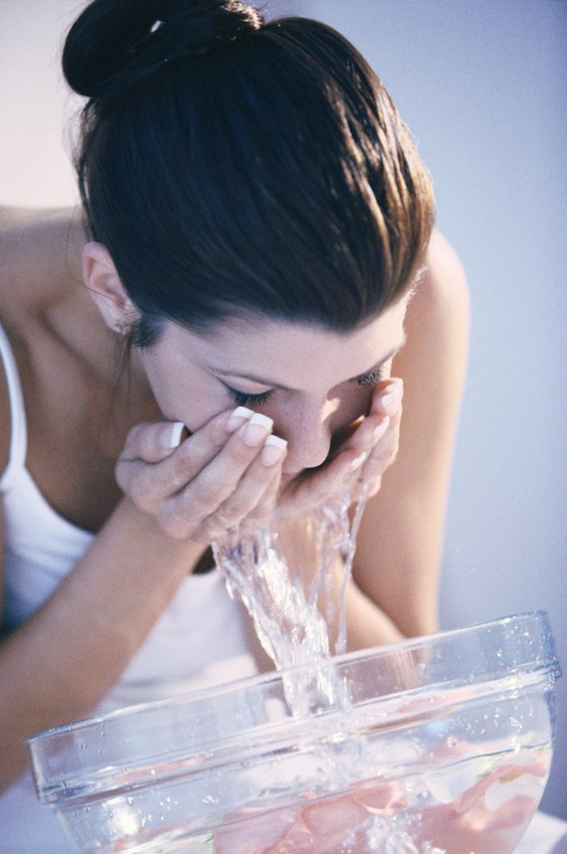 Young woman washing her face in a bowl of water