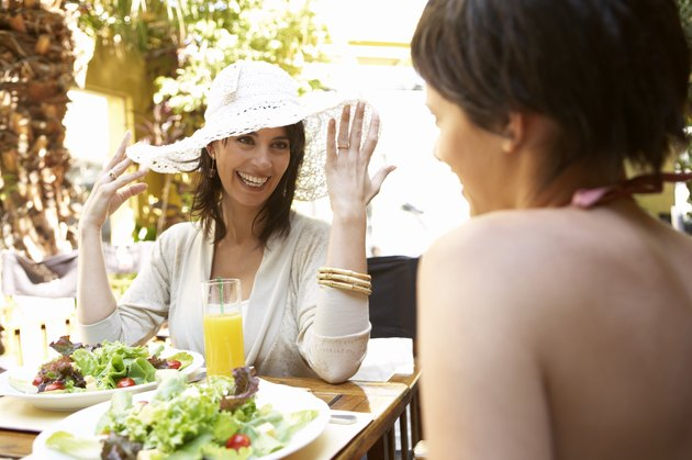 Two women at restaurant table, one touching brim of hat, smiling