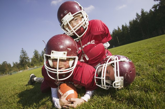 Three kids playing football