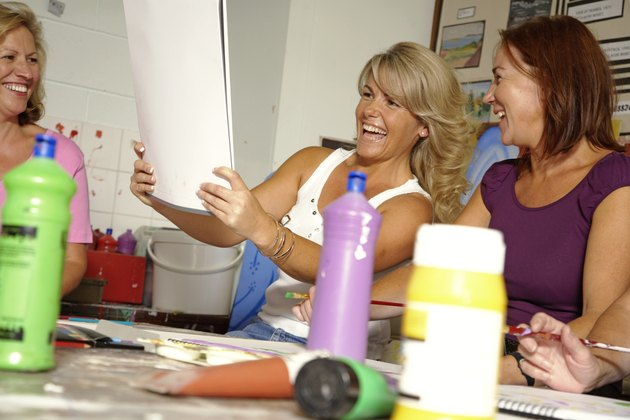Mature women in art classroom, one holding up painting, laughing
