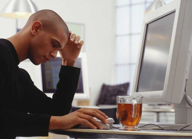 Thoughtful man using computer at Internet cafe, side view