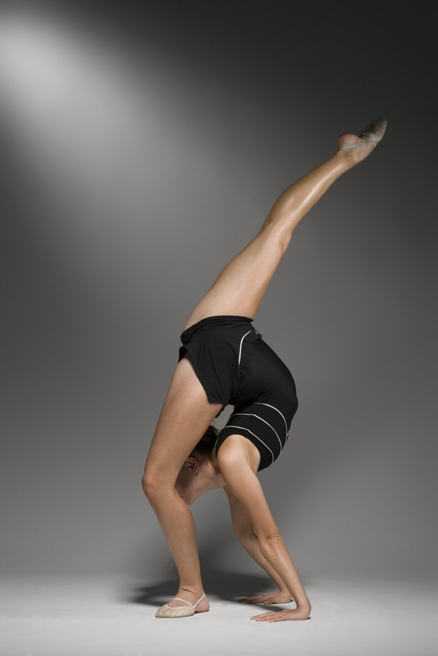 Female gymnast stretching, studio shot