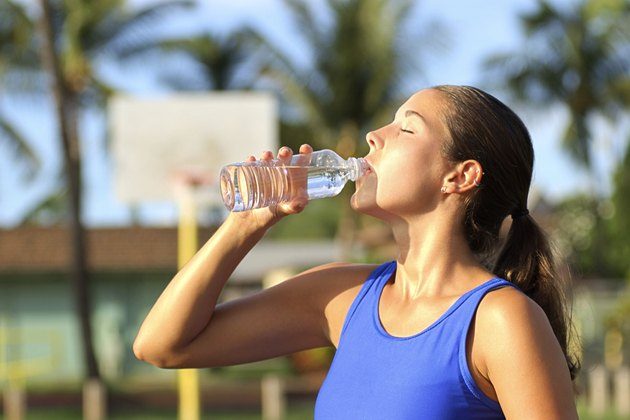 Side view of a woman drinking water from a bottle after exercising