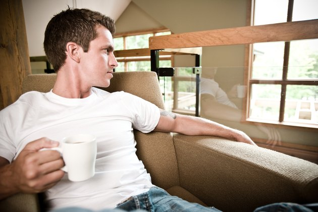 Man relaxing at home with cup of coffee