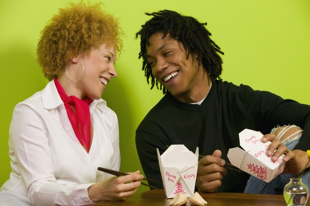 African couple eating takeout food