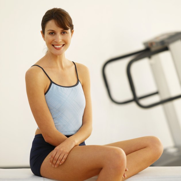 Smiling woman in sports gear sitting on a bench with treadmill in background