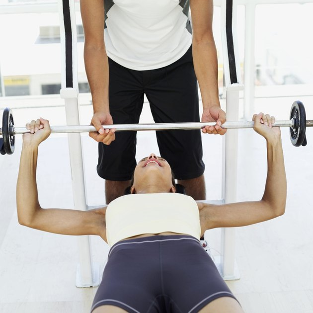 male instructor helping a young woman exercise with weights