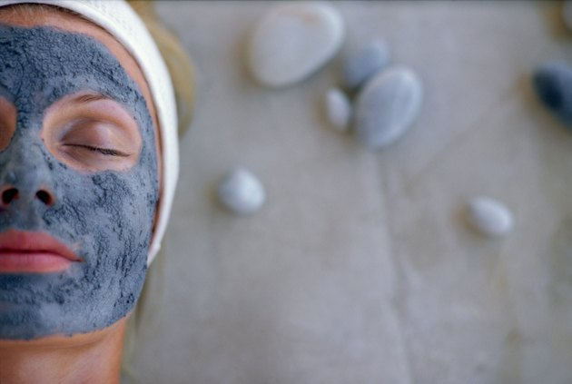 Woman with eyes closed wearing mud mask