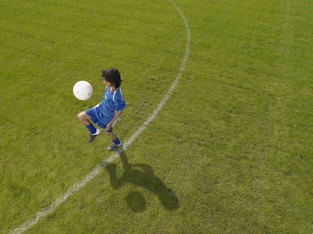Boy (8-10) footballer practicing skills, elevated view