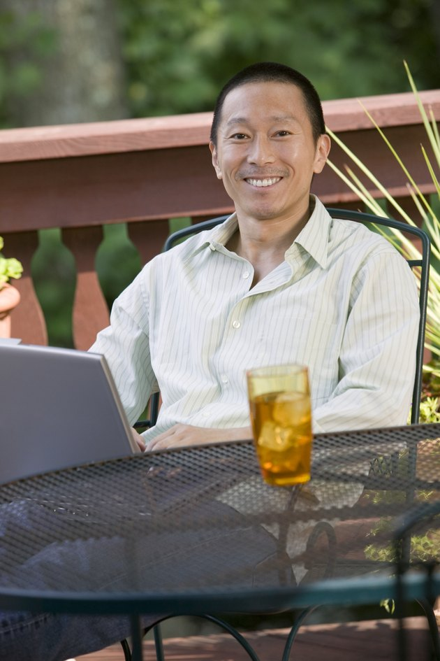 Man sitting outdoors with drink and laptop