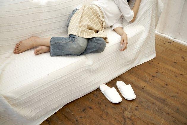 Woman wearing apron lying on sofa in living room