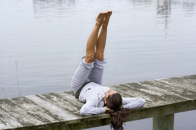 Young woman exercising on dock, rear view, close-up
