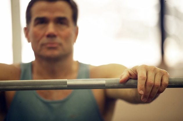 Close-up of a mature man exercising with a barbell