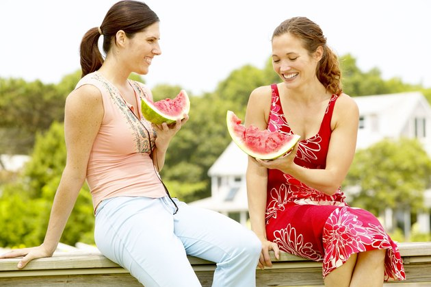 Women eating watermelon outdoors
