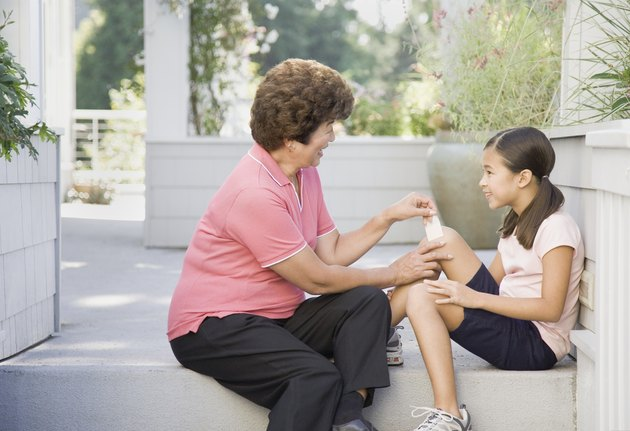 Asian grandmother putting bandage on granddaughter's knee on porch
