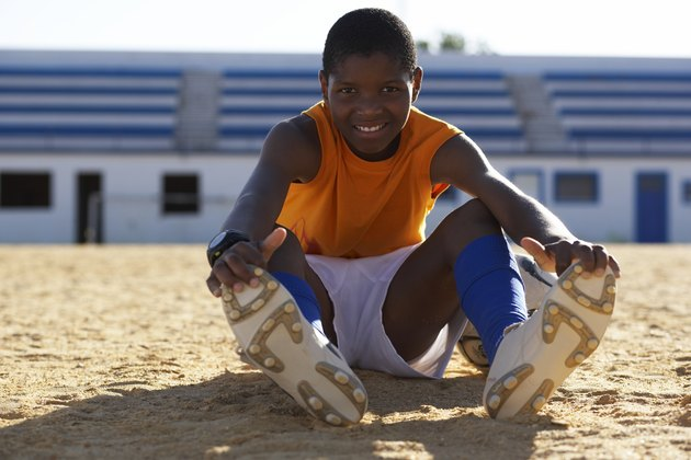 Portrait of boy (10-11) sitting on playing field, stretching