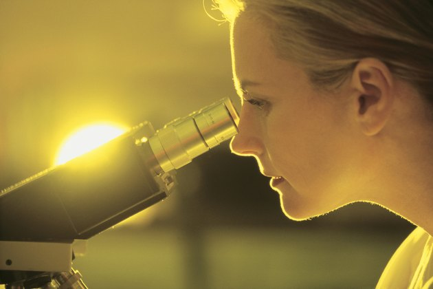 Woman scientist looking through microscope
