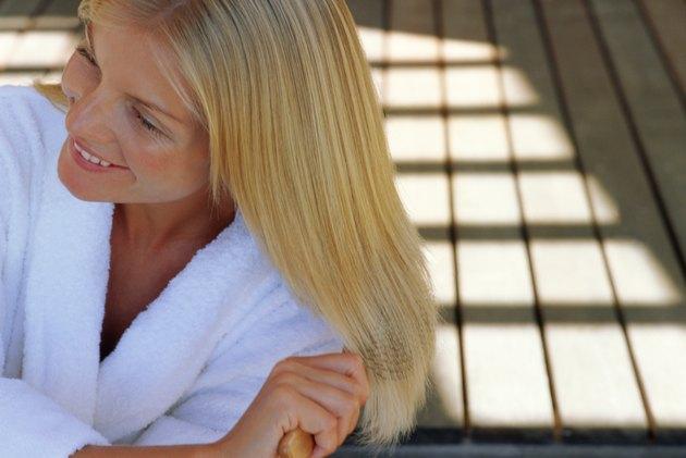Woman in bathrobe brushing hair outdoors