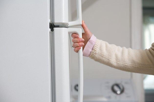 Hand of woman opening refrigerator door
