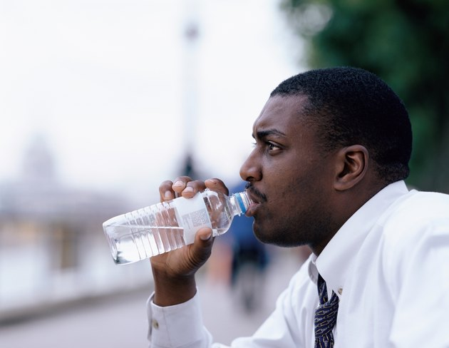 Side profile of a young man drinking water from a bottle outdoors