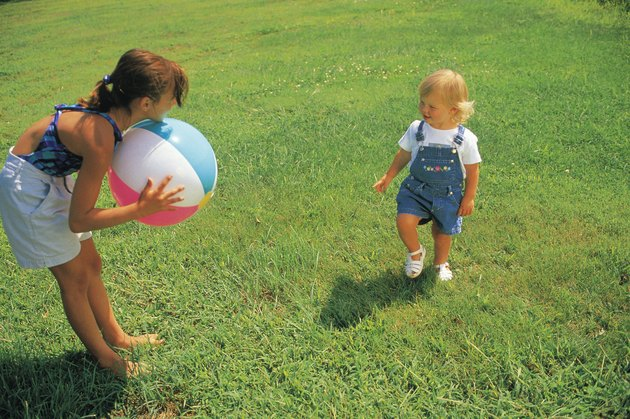 Girl and baby sister playing with beach ball