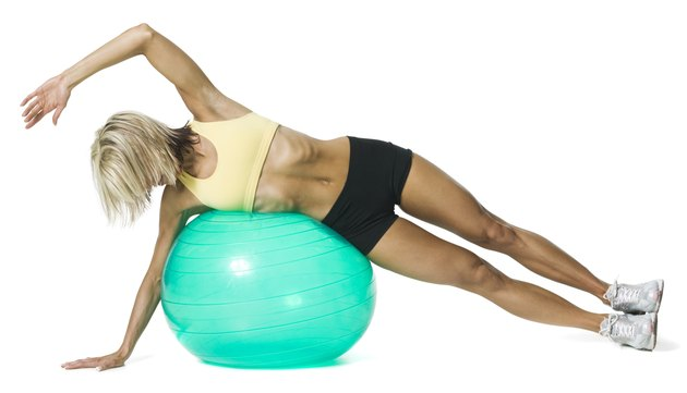 full body shot of a young adult woman in a yellow sports bra as she sretches out with a ball