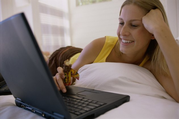 Close-up of a young woman lying on the bed and using a laptop