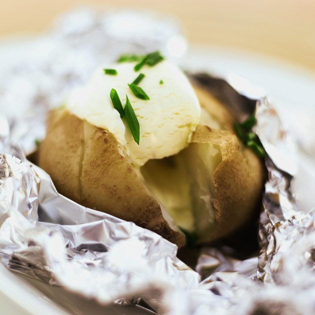 close-up of baked potato served with sour cream in foil