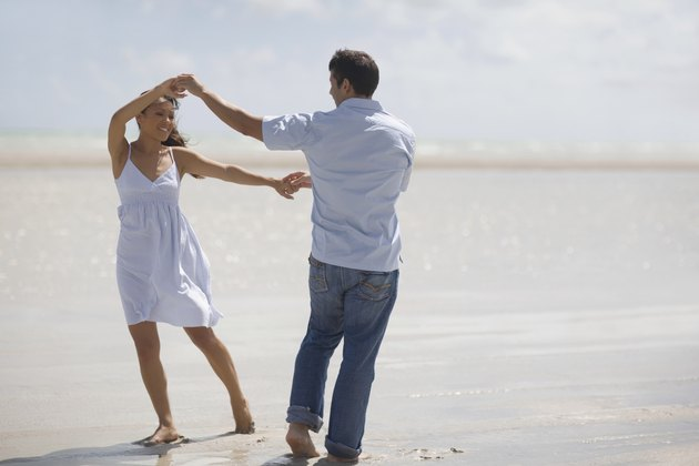 Hispanic couple dancing at beach