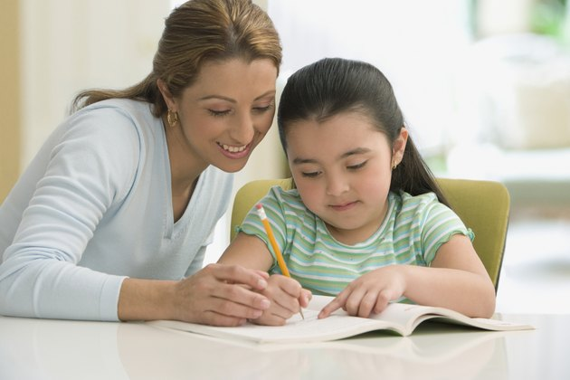 Hispanic mother helping daughter with homework