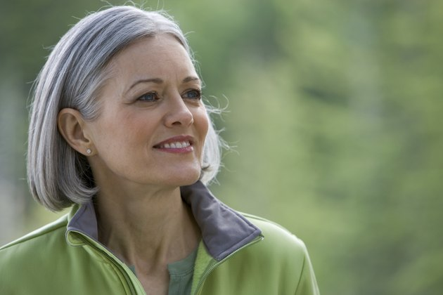 Mature woman with long grey hair looking aside, close-up