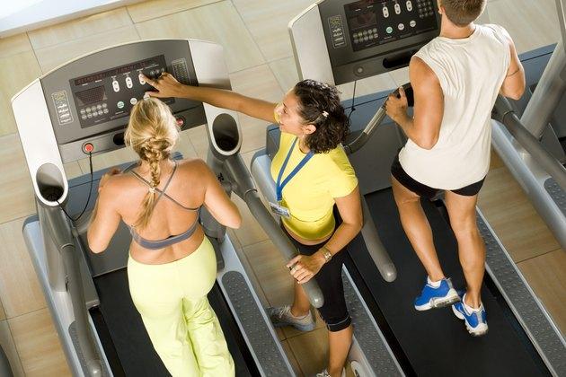 Instructor adjusting treadmill