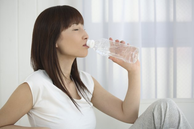 Young Woman Drinking Bottle of Water, Side View
