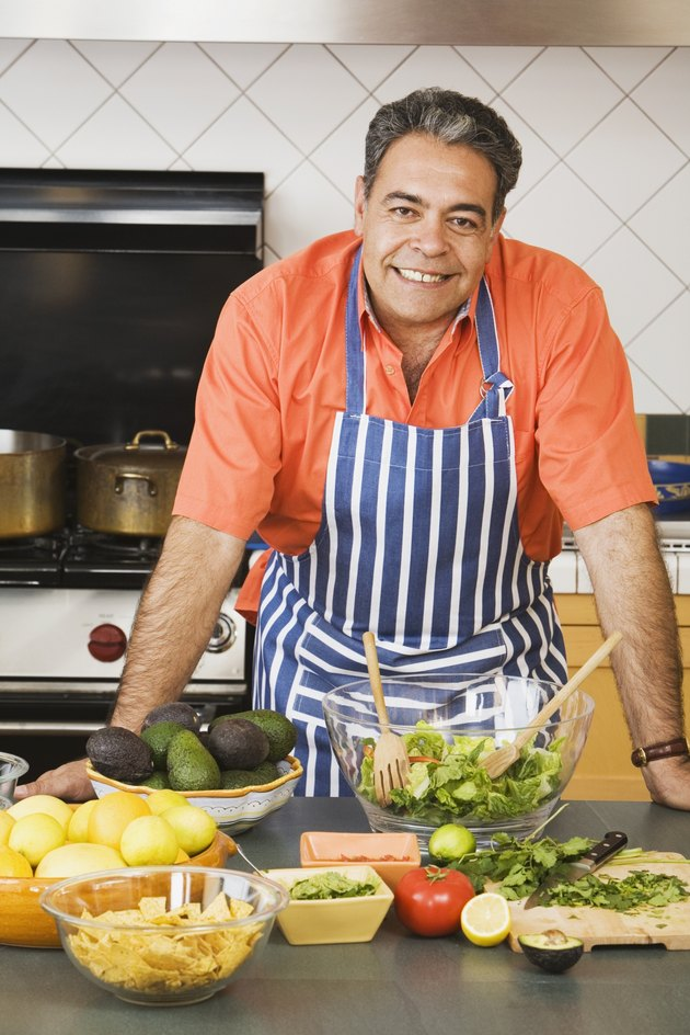 Middle-aged Hispanic man next to food in kitchen