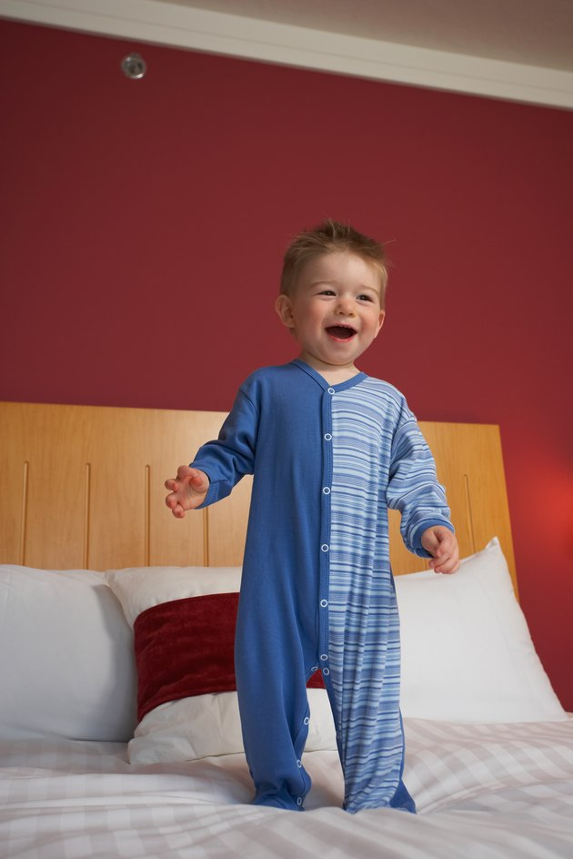 Smiling toddler boy standing atop hotel bed