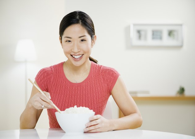Asian woman eating bowl of rice