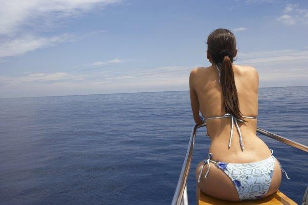 Hispanic woman on bow of boat