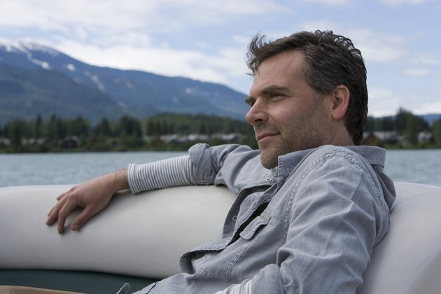 Mature man relaxing in inflatable raft on lake, close-up