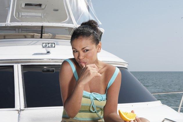 Mid adult woman eating orange on boat
